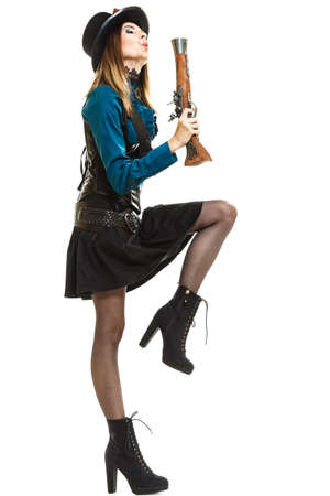 clothes interesting: Young steampunk islolated girl on white holding and blowing up fancy rifle making interesting motion. Fantasy old fashion with hat goggle. Stock Photo