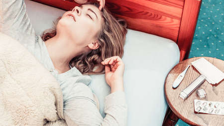 cold woman: Sick woman suffering from headache pain. Ill girl laying in bed caught cold. Thermometer and pills on table. Stock Photo