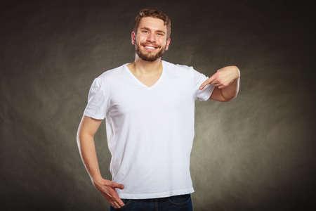 bonhomme blanc: Portrait de l'heureux bel homme décontracté à la mode en chemise blanche blanc avec copie espace vide en montrant lui-même. Jeune homme en studio sur fond noir. Mode annonce.