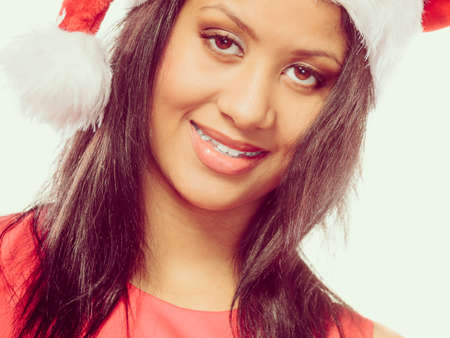 santa helper: Christmas winter happiness concept. Young woman girl mixed race wearing santa helper hat portrait.