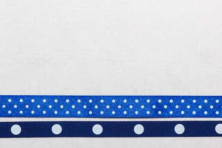 navy blue background: Festive celebration party frame. Polka dot navy blue satin ribbon on white cloth background Stock Photo
