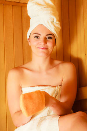 exfoliation: Spa beauty treatment and relaxation concept. Woman white towel relaxing in wooden sauna room, making massage with exfoliation glove