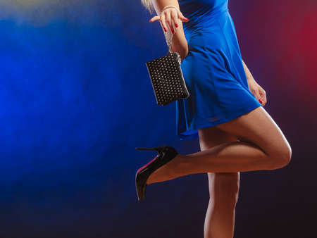 dancing club: Celebration disco and evening fashion concept - woman in blue dress holding handbag bag, dancing in the club, part of body female legs in high heels on party floor