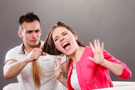 abusing: Husband abusing wife pulling her hair. Afraid and scared woman screaming, shouting and crying. Domestic violence aggression. Stock Photo
