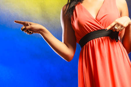club dress: Party, new year, celebration, disco concept. Woman part body in evening dress showing something finger, in club.