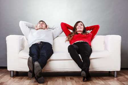 arms behind head: Happy, smiling young couple relaxing on couch at home. Calm, carefree man and woman resting with arms behind head. Healthy relationship. Stock Photo