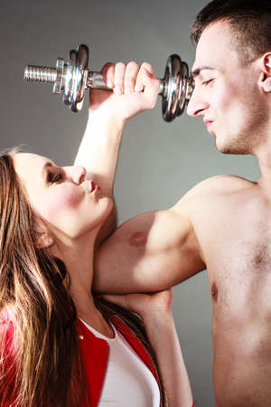 Bodybuilding. Strong man exercising with dumbbells. Closeup muscular guy flexing lifting weights, girl looking admiringly kissing his biceps. Stock Photo