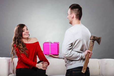insincere: Sneaky insincere man holding axe giving gift present box to woman. Husband concealing hiding his true feelings from happy trusting wife. Untrue False intention. Relationship problems.