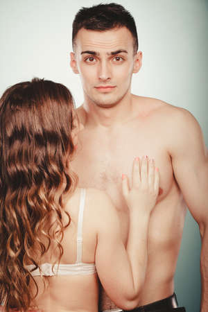 semi nude: Seductive alluring passionate young couple lovers embracing in studio. Handsome muscled half naked semi nude man and woman in lingerie. Love and passion. Stock Photo