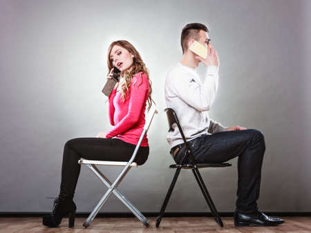 pensiveness: Young couple talking on mobile phones sitting back to back. Pensive woman and thoughtful man making a call. Wife and husband bored with relationship. Communication concept. Studio shot.