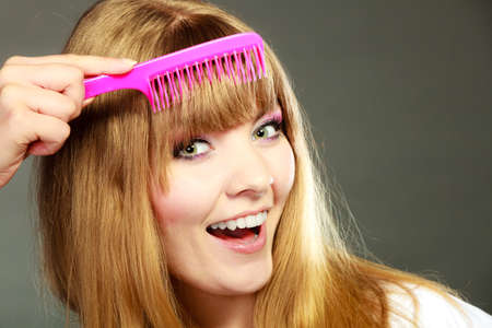 Fashion beauty and haircare concept. Closeup young woman refreshing her hairstyle she combing her hair fringe with pink comb