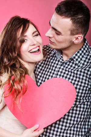 blinking: Romantic couple on valentines day. Happy joyful man and blinking woman holding heart symbol. Love concept.