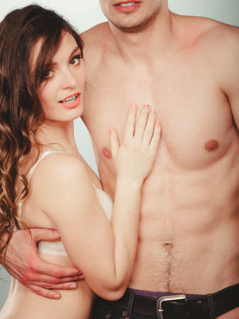 semi nude: Sexy passionate young couple lovers embracing in studio. Muscled half naked semi nude man and pretty gorgeous woman in lingerie. Love and passion.