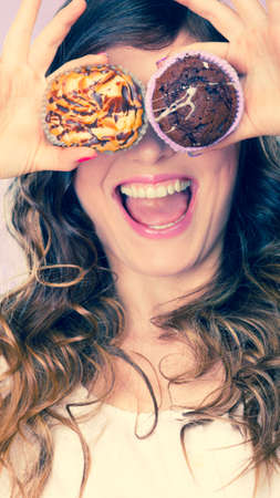 hands covering eyes: Bakery, sweet food and happiness concept. Closeup smiling woman having fun holding cakes in hands covering eyes with cupcakes Stock Photo