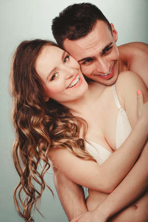 semi nude: Happy smiling sexy passionate young couple lovers embracing in studio. Handsome muscled half naked semi nude man and pretty gorgeous woman in lingerie. Love and passion.