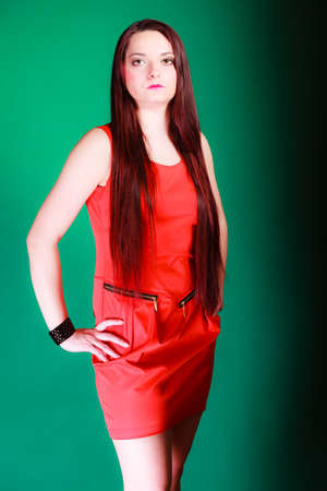 log hair: Party, celebration and date concept. Attractive young log hair woman in red dress on green background. Studio shot.