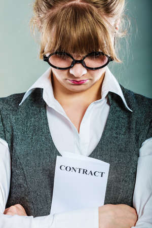 business skeptical: Business documents legal concept - closeup skeptical unhappy businesswoman holding contract in hands. Negative human emotion face expression feeling reaction