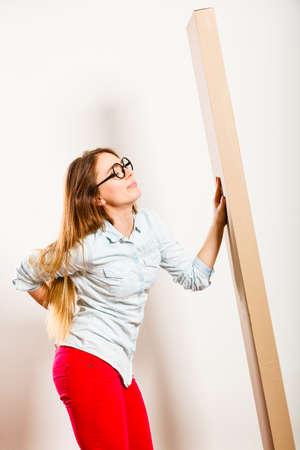 drained: Unhappy tired woman moving into new apartment house carrying heavy carton box with furniture. Young girl arranging interior and unpacking. Female having backache pain. Stock Photo