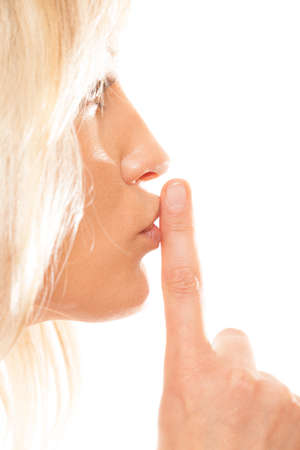 sigilo: Woman asking for silence or secrecy with finger on lips hush hand gesture. Isolated