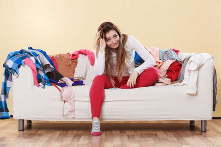 messy room: Desperate helpless woman sitting on sofa couch in messy living room with hand on head. Young girl surrounded by many stack of clothes. Disorder and mess at home.