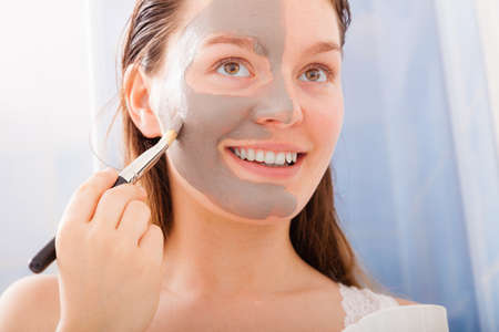 Beauty procedures skin care concept. Young woman no makeup applying facial gray mud clay mask to her face in bathroom using brush