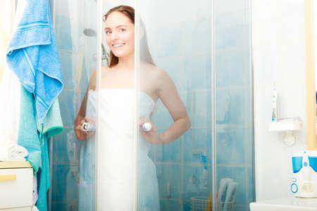 duschkabine: Girl showering in shower cabin cubicle enclosure. Young woman with white towel taking care of hygiene in bathroom. Lizenzfreie Bilder
