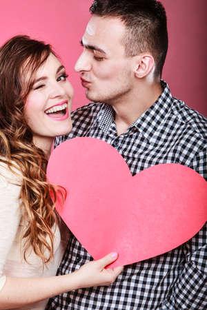 romantico: Pareja rom�ntica en el d�a de San Valent�n. Feliz hombre alegre y parpadeando mujer que sostiene el s�mbolo del coraz�n. Concepto del amor.