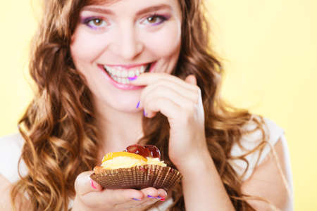 sweetness: Sweetness and happiness concept. Closeup cute flirty woman eating fruit cake licks fingers yellow background