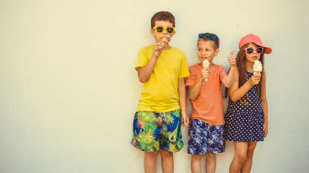 Kids eating gelato and soft serve ice cream. Boys and little girl in sunglasses enjoying summer holidays vacation.