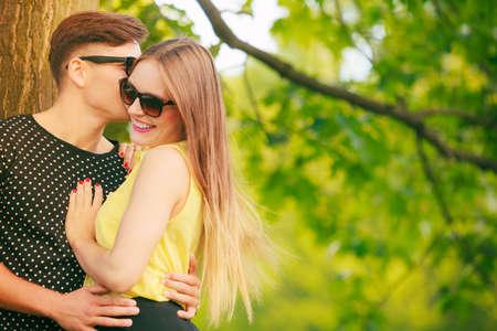 amantes: Amor y felicidad. Amantes Joven pareja feliz con gafas de sol contactos en el parque de verano al aire libre. Hombre susurro tomando a la mujer oído.