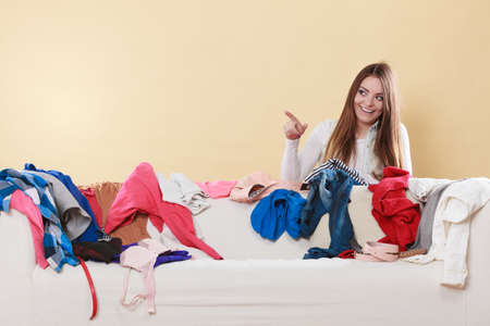 living things: Happy woman behind sofa couch in messy living room pointing at empty blank copy space. Young girl surrounded by many stack of clothes. Disorder and mess at home.