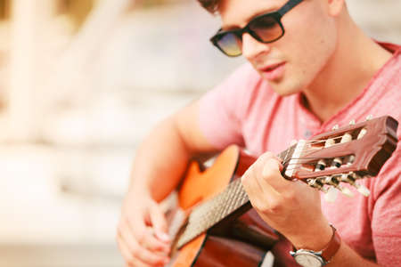 acoustic guitar: Performance and show time. Young fashionable man wearing sunglasses playing classic guitar outdoor.