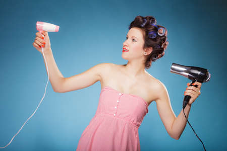drier: Young woman preparing to party having fun, funny girl styling hair with two hairdreyers retro style on blue