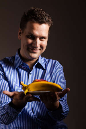 recommending: Diet and nutrition. Happy young man holding fruits on dark gray. Guy recommending healthy nutrition. Stock Photo