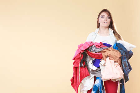 Young woman carrying stack pile of dirty laundry clothes. Girl cleaning tidying in studio with empty blank copy space.