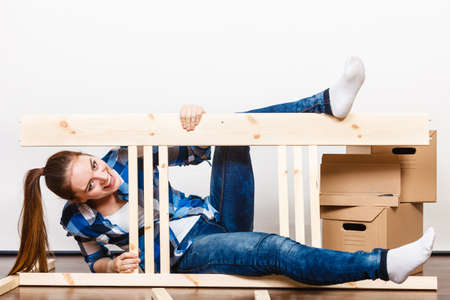 relocate: Happy woman moving in having fun assembling furniture at new home. Crazy young girl arranging apartment house interior and unpacking boxes. DIY. Stock Photo