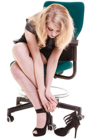 stoppage: Work stoppage and leg pain. Tired businesswoman woman sitting on chair and taking shoes off isolated on white. Business. Stock Photo