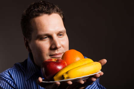 recommending: Diet and nutrition. Happy young man smelling fruits on dark gray. Guy recommending healthy nutrition.