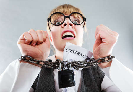chained: Business and stress concept. Furious businesswoman in glasses with chained hands holding contract grunge background unusual angle view