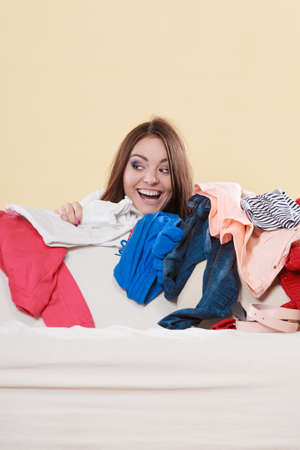 messy room: Happy woman behind sofa couch in messy living room. Young girl surrounded by many stack of clothes. Disorder and mess at home. Stock Photo