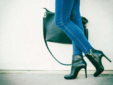 moda: Equipamento da forma de Outono. Mulher elegante longas pernas em calças jeans preto elegantes sapatos de salto alto e bolsa ao ar livre na rua da cidade