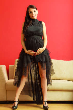 mothering: Stylish pretty girl in black evening dress. Pregnant woman preparing for event. Prospective mothering concept. Stock Photo