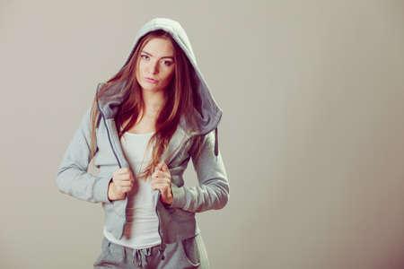 sweatshirt: Pensive thoughtful teenager girl wearing sweatshirt with hood and white shirt. Teen fashion. Studio shot.