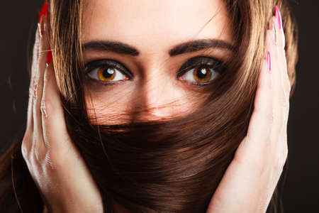 Close up woman covers the face by long brown hairs brown eyes with dark makeup