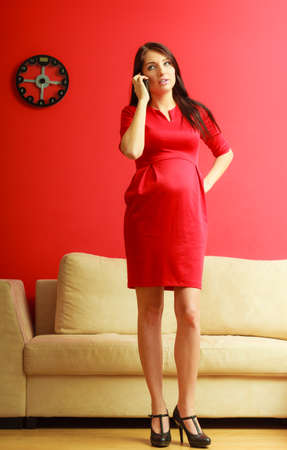 Stylish pretty girl in red dress. Pregnant woman talking on cellular phone at home. Prospective mothering using technology concept. Stock Photo