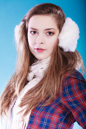 earmuff: Portrait of pretty woman in winter fashion. White earmuff, cold time.
