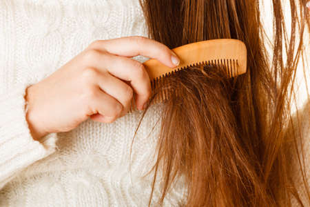 damaged: Female hand combing with brush her dry damaged long hair. Daily preparation for looking nice.