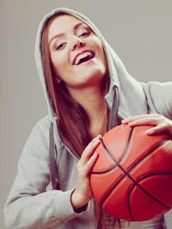 hooded sweatshirt: Happy sporty teenager girl wearing hooded sweatshirt holding basketball. Teen sport. Stock Photo