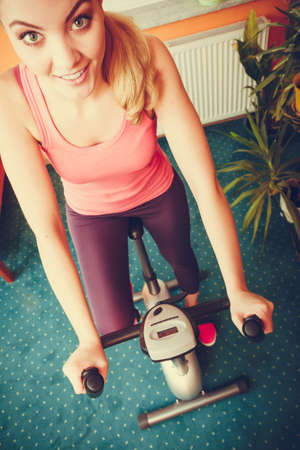 stationary bicycle: Active young woman working out on exercise bike stationary bicycle. Sporty girl training at home. Fitness and weight loss concept. High angle view.