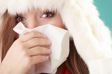 chory: Chora kobieta w futra kapelusz kichanie w tkance. Chora dziewczyna złapany zima zimny grypa w studio na zielono. Zdjęcie Seryjne